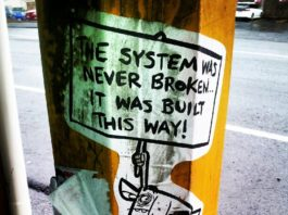 "Photo of ""The System is Never Broken"" sign"