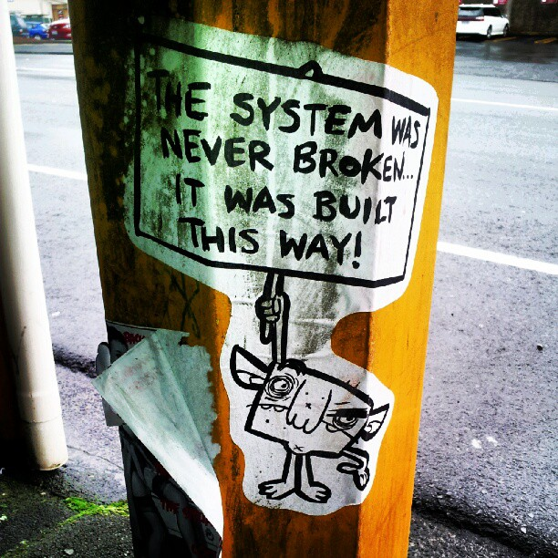 """Photo of """"The System is Never Broken"""" sign"""